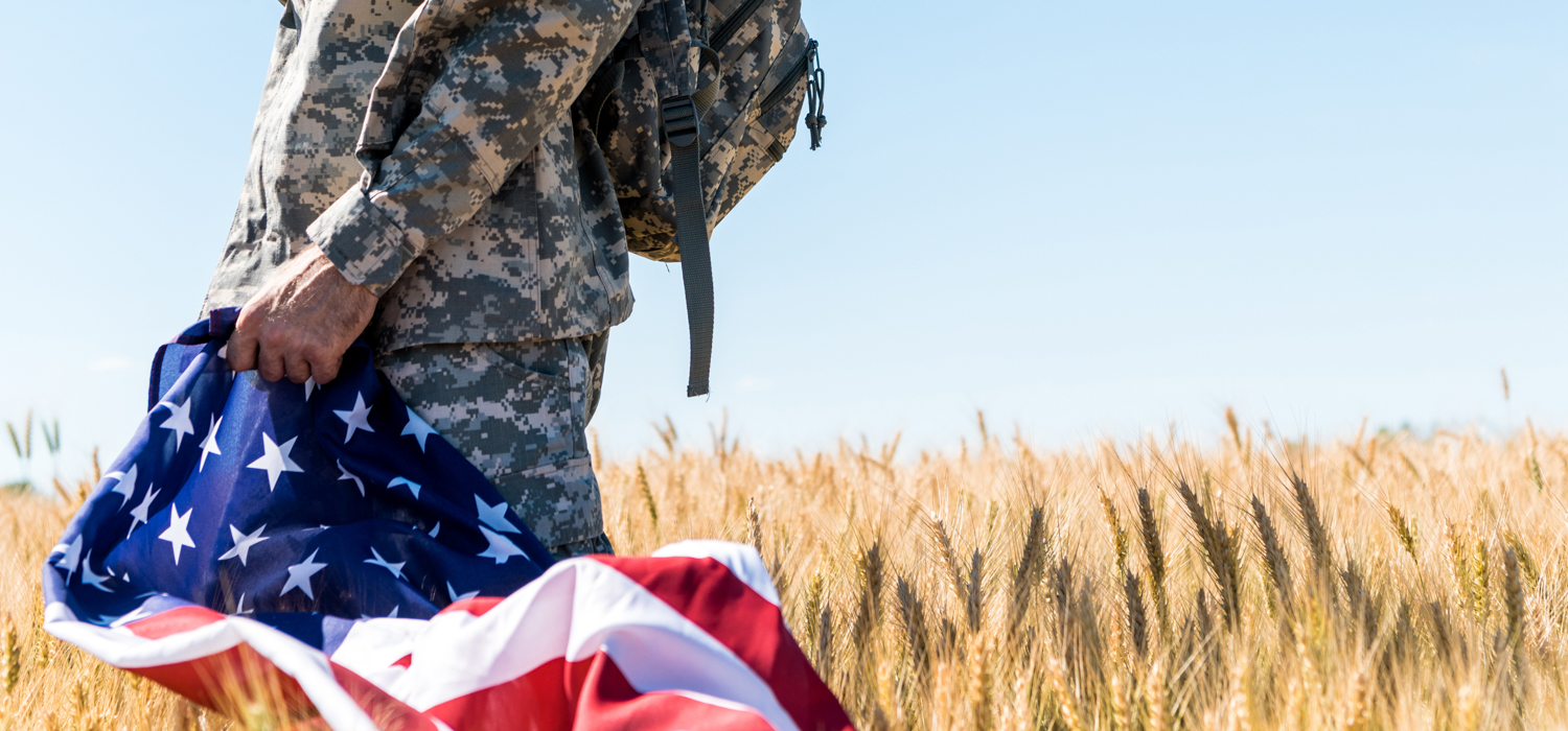 Patriotic soldier in military uniform holding American flag while standing in field